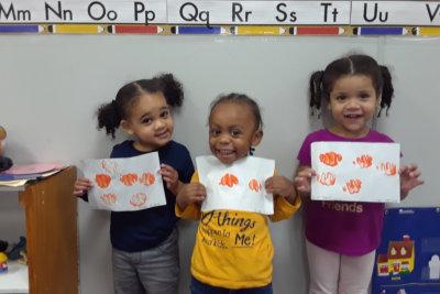 three little girls presenting their art work